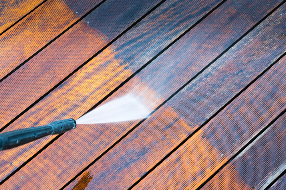pressure washer working on an exterior deck