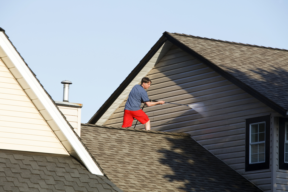 man pressure washing a house with one of the best pressure washers for diyers